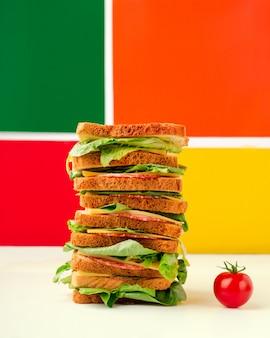 Гигантский многослойный бутерброд с салями и сыром, маленький помидор