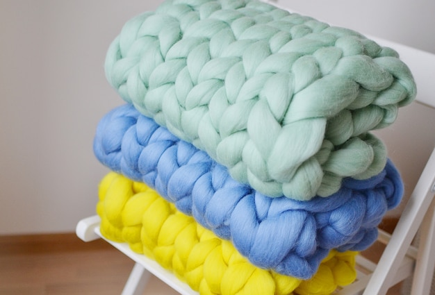 Giant pink mint yellow blue blanket plaid merino wool knitted on white wooden stool chair home interior