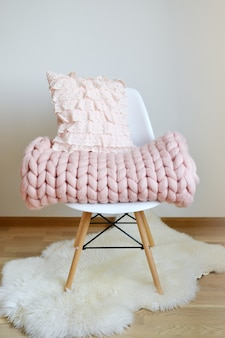 Giant pink plaid blanket woolen knitted on white wooden stool chair home scandinavian style