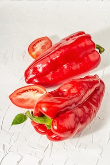 Giant red bell peppers and tomatoes on white background. sweet vegetable, new harvest, fresh ingredient for healthy food, close up