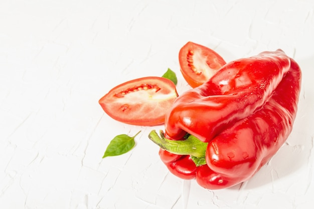 Giant red bell peppers and tomatoes on white background. sweet vegetable, new harvest, fresh ingredient for healthy food, copy space