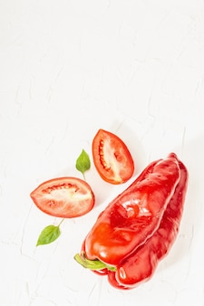 Giant red bell peppers and tomatoes on white background. sweet vegetable, new harvest, fresh ingredient for healthy food, top view