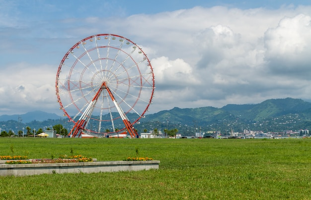 Giant red and white ferris wheel with mountains