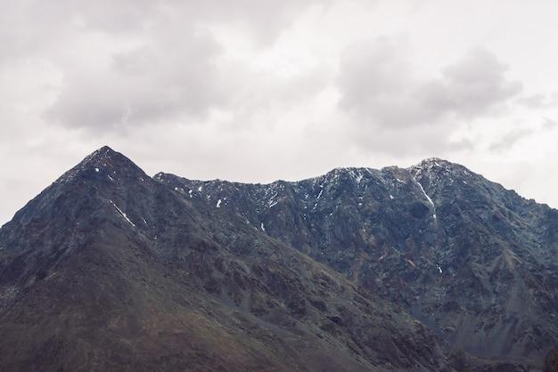 Гигантский хребет со снегом под пасмурным небом. атмосферный туманный скалистый склон горы. удивительный горный массив в пасмурную погоду. необычные туманные скалы. прекрасный пейзаж величественной природы высокогорья.