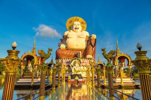Giant smiling or happy buddha statue in wat plai laem temple, samui, thailand