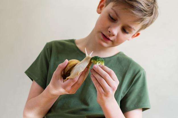 巨大なカタツムリのペット大きな国内のカタツムリachatinaを持つ10代の少年