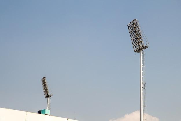 巨大なスポットライトは、空の背景と高いポールにスタジアムにあります