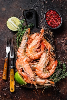 Giant tiger prawns shrimps on a cutting board with herbs