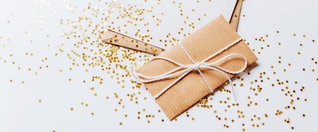 封筒、白い背景の上の金のキラキラ星とギフトと空白のメモ