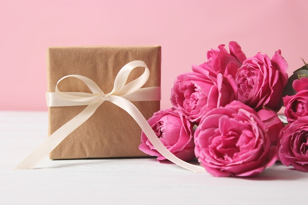 Подарок и цветы на цветном фоне праздника дарят в подарок поздравление