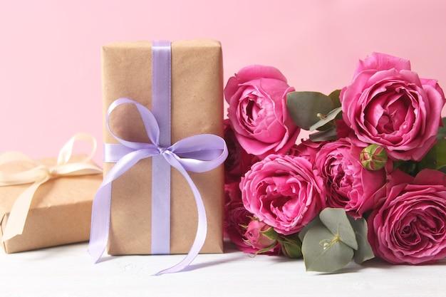 色付きの背景の休日の贈り物と花は贈り物おめでとうを与えます