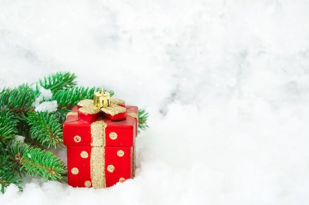 雪のコピースペースでギフトと松の木の枝