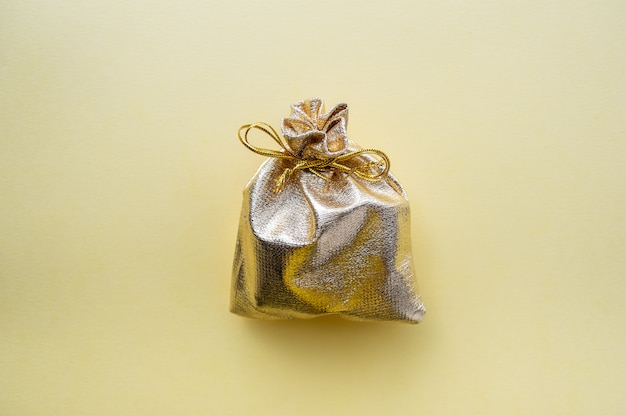 Gift bag of golden fabric on a yellow background.