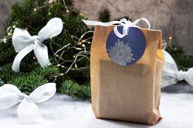 Gift in a bag made of kraft paper, against the background of a spruce wreath and garland. selective focus.