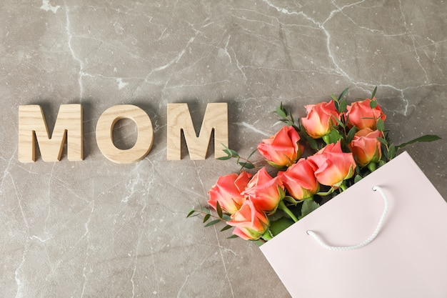 Gift bag with bouquet of orange roses and inscription mom on brown table, top view