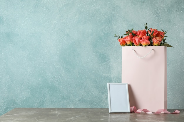 Gift bag with bouquet of pink roses and empty frame on grey table