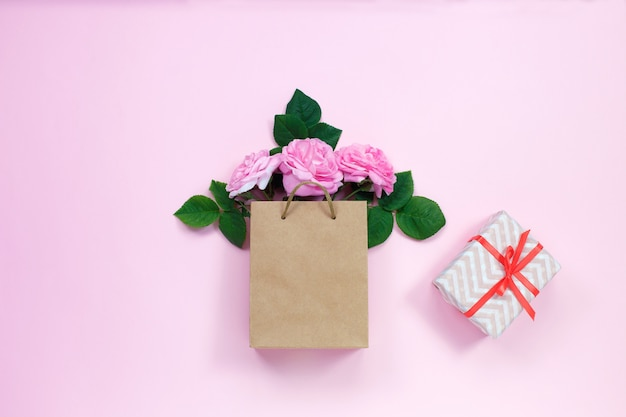 Gift bag with bouquet of pink roses and gift box