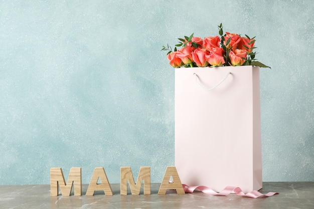 Gift bag with bouquet of pink roses and inscription mom on grey table