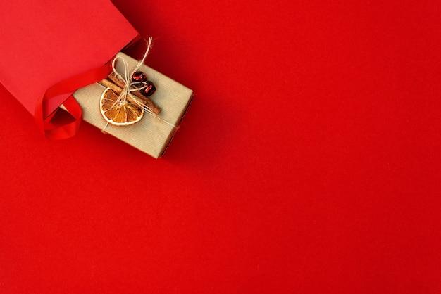 Подарочный пакет с украшенной коробкой на красном фоне. приготовление, покупка подарков, распродажа на новый год и рождество. копирование пространства, вид сверху, плоская планировка.