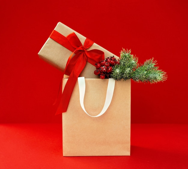Подарочный пакет с украшенной крафт-коробкой с веточкой елки на красном фоне. приготовление, покупка подарков, распродажа на новый год и рождество.