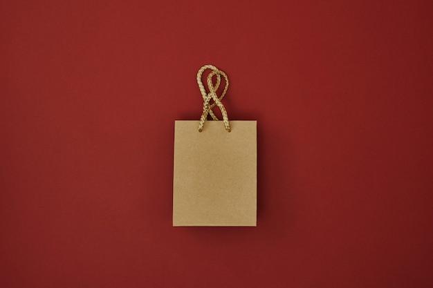 Подарочные пакеты на красном фоне копировать пространство плоский макет вид сверху