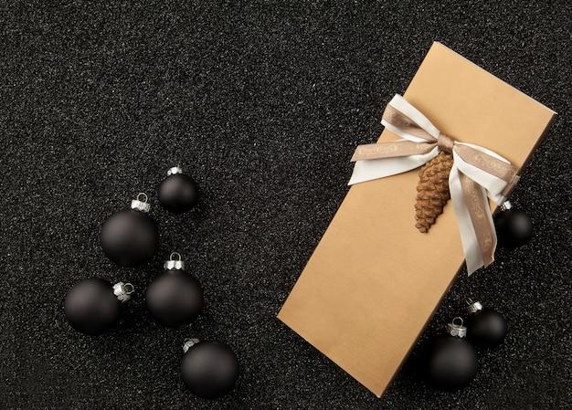 黒の粒子の粗い背景にクリスマスツリーの装飾が施されたギフトブックレット