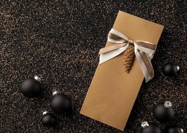 金色の粒子の粗い背景にクリスマスツリーの装飾が施されたギフトブックレットリボン付きチラシ