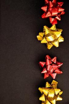 ギフトの弓は黒い背景に並んでいます。クリスマスと新年。誕生日プレゼント。テキストのための空のスペース。スタイリッシュな休日の背景。