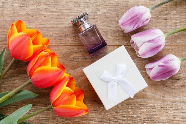 선물 상자, 나무 판자에 빨간색과 라일락 튤립이 있는 향수 한 병. 인사말 카드 개념입니다. 평면도.