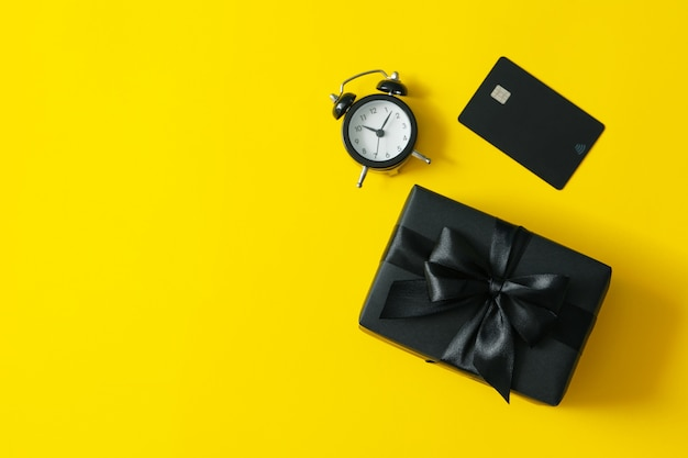 Gift box, alarm clock and card on yellow