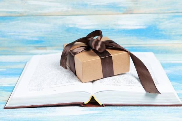Подарочная коробка и книга на столе