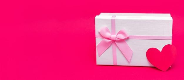 ピンク-赤の背景にハートの形のギフトボックスとカード。バレンタインデー、クリスマス、誕生日に愛を込めてギフトを贈りましょう。リボン付きの繊細な白いパッケージ。あなたの愛する人を驚かせましょう。幸せな休日。