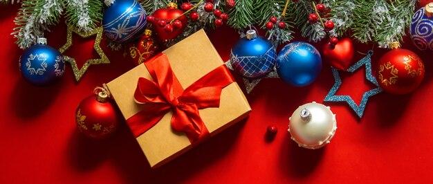 Подарочная коробка и рождественские украшения на ветке дерева