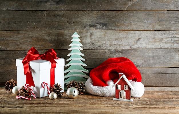 Подарочная коробка и рождественские украшения на деревянном столе