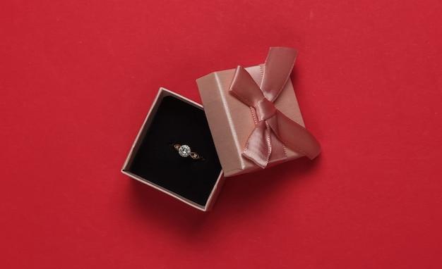 ギフトボックスと赤い背景にダイヤモンドの婚約金リング。結婚式、ロマンチックなコンセプト。宝石。上面図。フラットレイ
