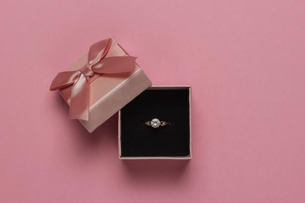 ピンクのパステルカラーの背景にダイヤモンドのギフトボックスと婚約金のリング。結婚式、ロマンチックなコンセプト。宝石。上面図。フラットレイ