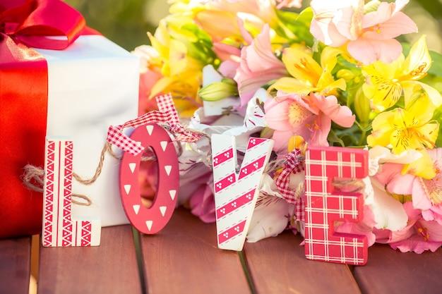 Подарочная коробка и цветы на фоне весны. концепция семейного отдыха. день матери