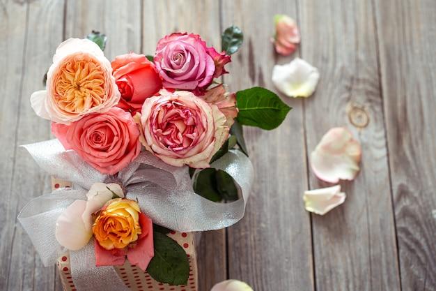 Подарочная коробка и свежие розы на деревянном фоне