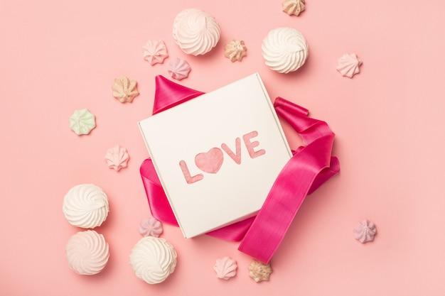 Подарочная коробка и подарочные конфеты, зефир и безе на пастельно-розовой поверхности