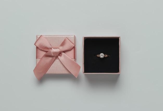 ピンクのパステルカラーの背景にダイヤモンドのギフトボックスとゴールドのリング。結婚式のコンセプト。宝石。上面図。フラットレイ