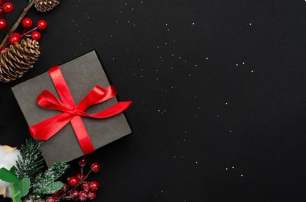 Подарочная коробка и вид сверху ягод холли ilex на черном фоне.