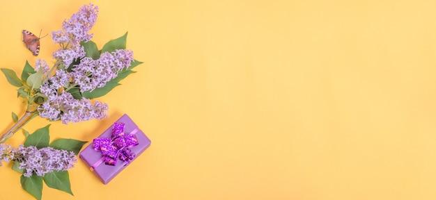Подарочная коробка и сиреневые цветы на желтом фоне с копией пространства