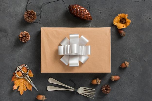 Расположение подарочной коробки и сосновых шишек