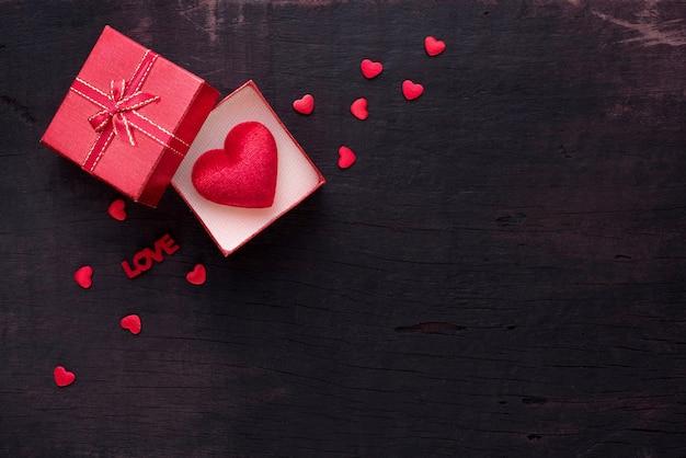 ギフトボックスと赤いハートは、愛の結婚式やバレンタインデーのためのコピースペースと黒い木の背景に上昇しました。