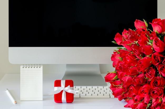 Подарочная коробка и букет красных роз на рабочем столе для концепции дня святого валентина.