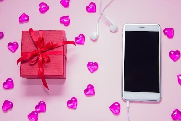 Подарочная коробка и смартфон на розовом фоне женский день подарочный офисный стол