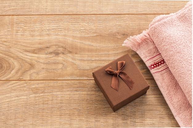 나무 배경에 선물 상자와 부드러운 테리 수건. 스파 및 바디케어 세트입니다. 휴일 인사말 개념입니다. 평면도.