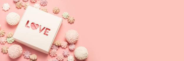 パステルピンクの表面にギフトボックスとお菓子