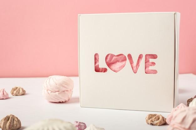Подарочная коробка и сладости на розовом фоне. концепция подарка дня святого валентина. баннер.