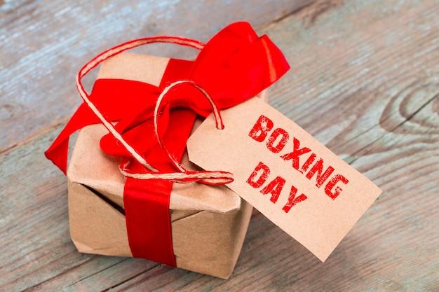 텍스트가 있는 선물 상자 및 태그: 박싱 데이, 나무 배경.